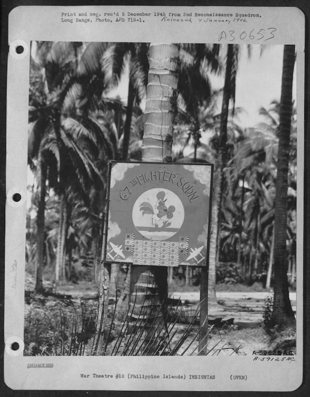 T/Sgt Ben Olbrich served with the 67th Fighter Squadron in the Philippines in the final part of World War II.  Olbrich was one of the original members of Oregon's 123rd Observation Squadron.  The squadron's famous Fighting Cock insignia seen posted near the unit's camp area on the island of Palawan in October, 1945, showing a total of 26 aerial victories in World War II.  Today the squadron flies the F-15C Eagle fighter at Kadena AB, Okinawa, Japan.  (NARA, via Fold3)