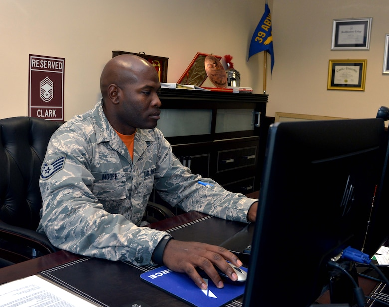 Staff Sgt. Antone Moore, 39th Communications Squadron Weapons and Storage and Security System radio frequency transmission systems supervisor, sits at Chief Master Sgt. Vegas Clark, 39th Air Base Wing command chiefs, desk Aug. 28, 2015, at Incirlik Air Base, Turkey. Moore took part in a one-day job shadow, which allowed him to see the ins and outs of being a command chief. (U.S. Air Force photo by Senior Airman Michael Battles/Released)