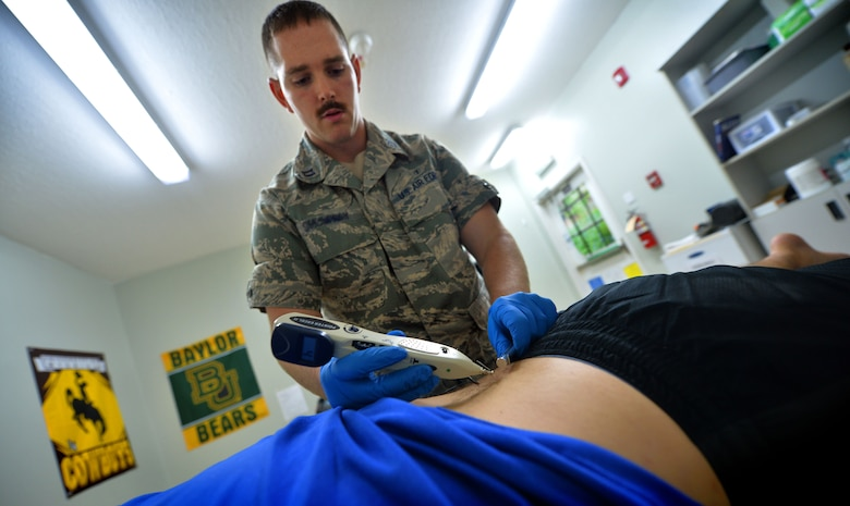 Capt. Joshua, 380th Expeditionary Medical Squadron physical therapist, applies heat to needles to help relieve a patient's back injury at an undisclosed location in Southwest Asia Sept. 1, 2015. The physical therapy team is responsible for evaluating patients and utilizing different therapeutic procedures to help restore patient functions. (U.S. Air Force photo/Tech. Sgt. Jeff Andrejcik)