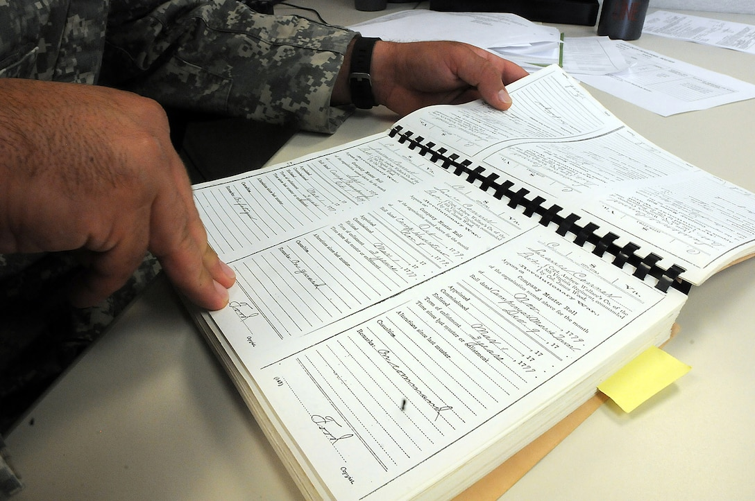 Staff Sgt. Joshua Conner reviews a copy of a company muster roll from his relative Lawrence Conner, who served with the 8th and 12th Virginia regiments during the Revolutionary War. The Conner family's historical record book holds family documents that date back to the beginnings of America. Among a collection of family military service in the book, J. Conner shares the story of his relative 1st. Lt. Garlin Murl Conner, World War II veteran, who is reportedly the second most decorated soldier from World War II. (U.S. Army photo by Spc. David Lietz/Released)