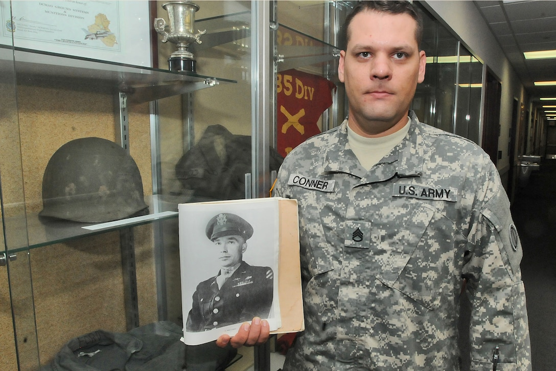 Staff Sgt. Joshua Conner holds a photograph of his relative 1st Lt. Garlin Murl Conner, World War II veteran. According to various news reports, G. Conner is the second most decorated soldier from World War II.