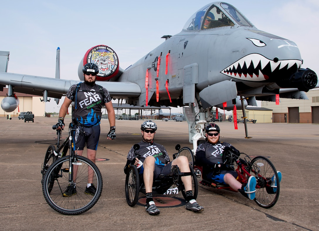 Jarrod Smith, (left), Clay Jacobs, (middle), and Christopher Freeman, (right), take a break at a rest stop at Sheppard Air Force Base, Texas, during the Hotter'N Hell 100 bike race Aug. 29, 2015. Freeman is a veteran who was paralyzed from the waist down after a car accident in 2010. He has participated in three Hotter'N Hell rides since the accident to share his story of resiliency with other riders, and observers along the route. (U.S. Air Force photo by Danny Webb)