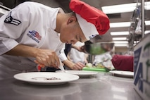 "Airman 1st Class Ruel Abastas, a 90th Force Support Squadron chef, decorates a plate with chocolate syrup for a dessert dish during an ""Iron Chef"" competition at the Chadwell Dining Facility on F.E. Warren Air Force Base, Wyo., Aug. 27, 2015. Chefs from the 90th FSS had to create an entree incorporating the secret ingredient, cheese crackers with peanut butter, along with a dessert dish within the hour time limit. (U.S. Air Force photo/Lan Kim)"