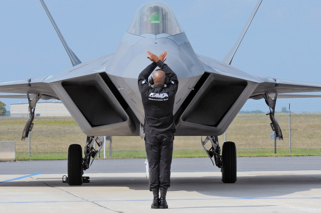 A crew chief with the Air Combat Command F-22 Raptor Demo Team taxis a Raptor onto the flightline at Atlantic City Air National Guard Base, N.J., Aug. 31, 2015. Two F-22s performed at the Atlantic City Airshow. (U.S. Air National Guard photo/Senior Airman Shane S. Karp)
