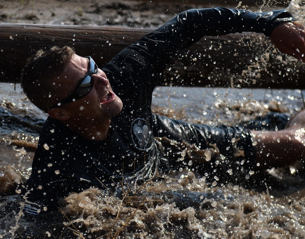 Chief Master Sgt. Wayne Stott, the 90th Medical Group superintendent, splashes through muddy water Aug. 29, 2015, during the second annual mud run at F.E. Warren Air Force Base, Wyo. The run attracted more than 100 Airmen and their families. (U.S. Air Force photo/Airman 1st Class Brandon Valle)