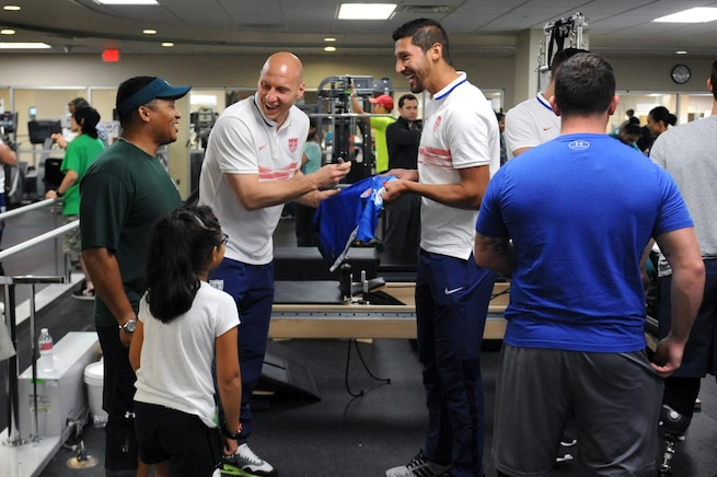U.S. Men's National Team members Brad Guzan, left, and Omar Gonzalez sign autographs for 8-year-old Lexi Terry, the daughter of Jae Terry, during an event with the soccer team and wounded warriors at Walter Reed National Medical Center in Bethesda, Md., Sept. 3, 2015. DoD photo by Marvin Lynchard