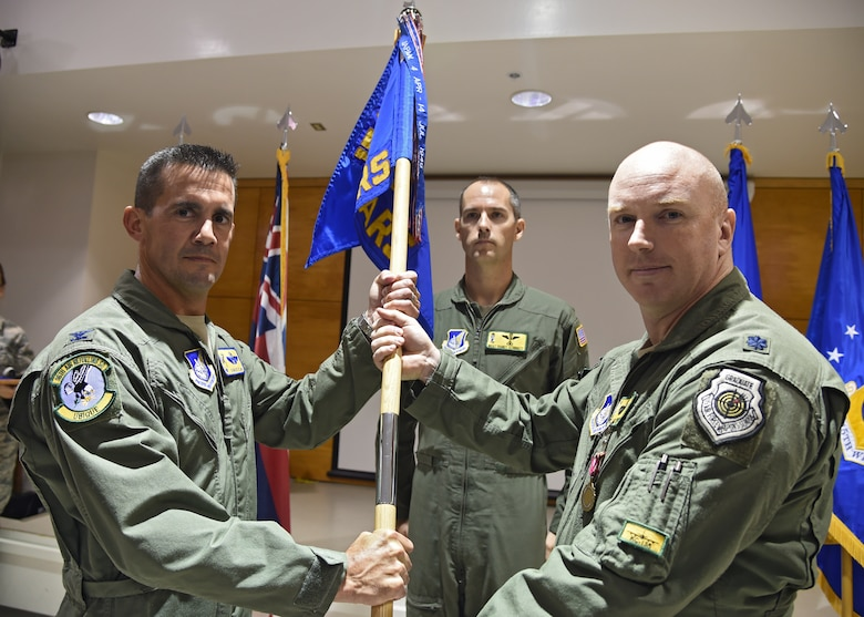 Col. Charles Velino, 15th Operations Group commander, receives the guidon as Lt. Col. Jason Work, 96th Air Refueling Squadron commander, relinquishes command during the 96th ARS deactivation ceremony on Joint Base Pearl Harbor-Hickam, Hawaii, Sept. 3, 2015. The 96th Air Refueling Squadron was reactivated on July 23, 2010, at Joint Base Pearl Harbor Hickam, in response to an increased demand for in-flight air refueling support throughout the Pacific theater. Since its reactivation, the 96th Air Refueling Squadron flew more than 1,800 sorties, totaling over 6,500 hours and offloading more than 36-million pounds of fuel to thousands of joint and multinational aircraft. (U.S. Air Force photo by Tech. Sgt. Aaron Oelrich/Released)