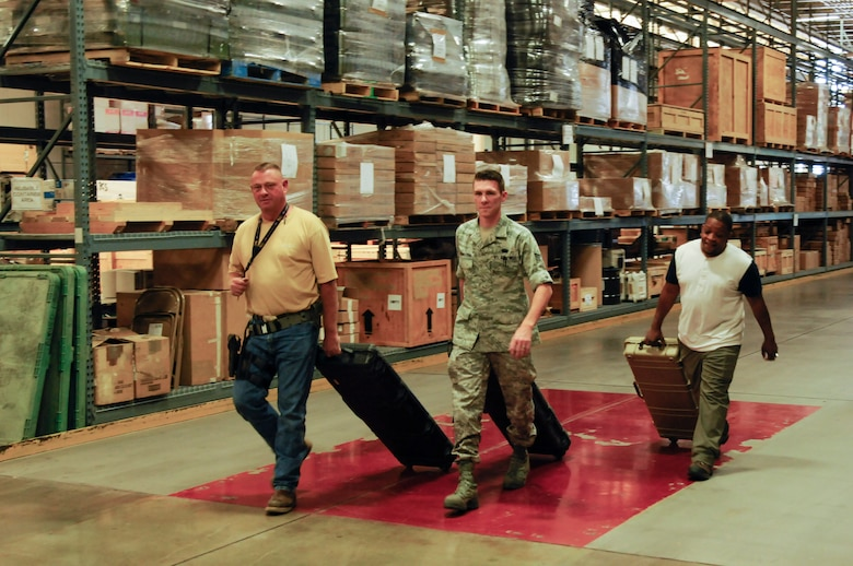 Brian Alexander, 90th Logistics Readiness Squadron materials handler; Senior Airman Andrew Leemasters, 90th LRS non-commissioned officer in charge of individual protection equipment; and Derrick McFadden, 90th LRS do-in-for maintenance monitor, roll cases with weapons to store in the armory of the 90th LRS Warehouse on F.E. Warren Air Force Base, Wyo., Sept. 2, 2015. The logistics Airmen placed the weapons in a secure storage unit for safekeeping until the weapons are needed again. (U.S. Air Force photo by Senior Airman Jason Wiese)