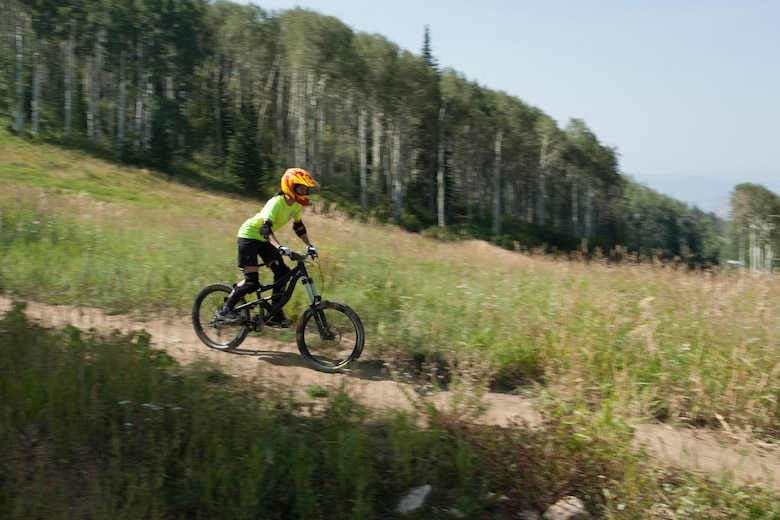 Staff Sgt. Ariadni Eyman, 90th Contracting Squadron, rides down a hill on a mountain biking trail on Mount Werner in the Routt National Forest, Colo., Aug. 29, 2015. It was Eyman's first time downhill mountain biking. (U.S. Air Force photo by Lan Kim)