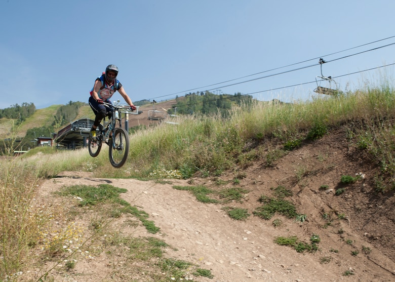 Staff Sgt. Dylan Haley, 90th Munitions Squadron, jumps a tabletop dirt mound at a bike park in Steamboat Springs, Colo., Aug. 29, 2015. The bike park is situated on Mount Werner in Routt National Park. (U.S. Air Force photo by Lan Kim)