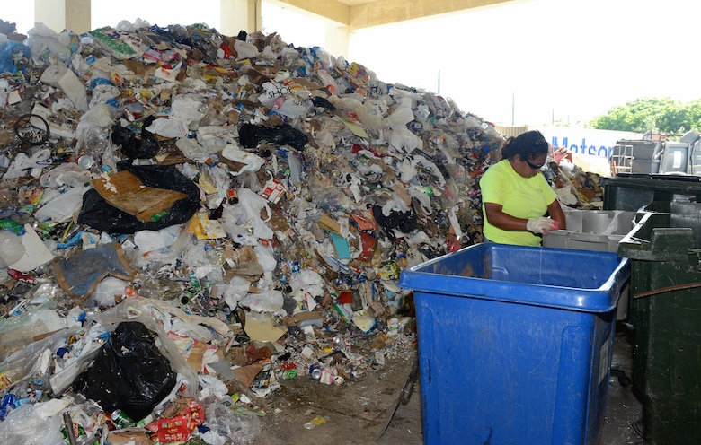 Jessica Dabinon, Arc Light Recycling Center refuse collector, separates recyclable material from a pile Aug. 28, 2015, at Andersen Air Force Base, Guam. The Arc Light Recycling Center's goal is to divert as much material out of the waste stream as possible. (U.S. Air Force photo by Airman 1st Class Arielle Vasquez/Released)