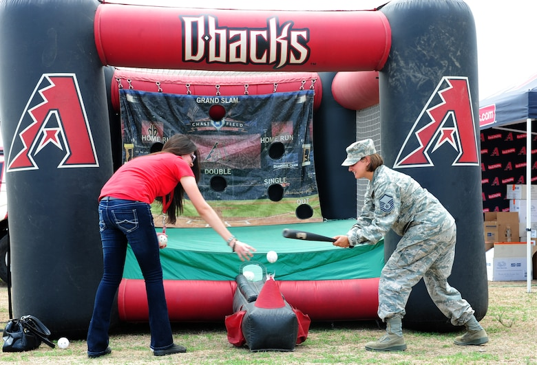 """U.S. Air Force Master Sgt. Chandra Barlow, 14th Reconnaissance Group NCO in charge of command support staff, plays T-ball with an Arizona Diamondback street team member during a """"Welcome Home"""" barbecue at Davis-Monthan Air Force Base Ariz., Sept. 3, 2015. The event was held by the Tucson community to show its appreciation towards the Airmen of D-M for all the work they have done during this past deployment cycle.  (U.S. Air Force photo by Airmen 1st Class Cheyenne A. Powers/Released)"""