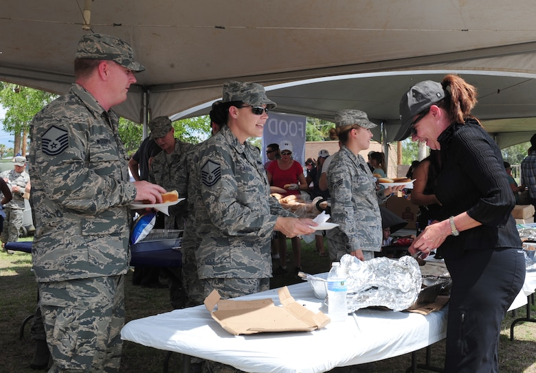 """Airmen are served food during a """"Welcome Home"""" barbecue at Davis-Monthan Air Force Base Ariz., Sept. 3, 2015. The Tucson community provided hamburgers, hotdogs, drinks, as well as entertainment for the D-M Airmen. (U.S. Air Force photo by Airmen 1st Class Cheyenne A. Powers/Released)"""