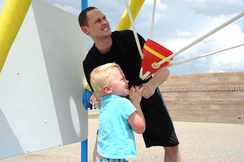 """U.S. Air Force 1st Lt. Corbin Lind, 355th Operations Group executive officer, and his son prepare to launch water-balloons in a water war Sept. 3, 2015, during a """"Welcome Home"""" barbecue at Davis-Monthan Air Force Base, Ariz.  The Tucson community provided activities ranging from water wars, paintball, live music and more for returning deployers and their families. (U.S. Air Force photo by Airman 1st Class Ashley Steffen/Released)"""