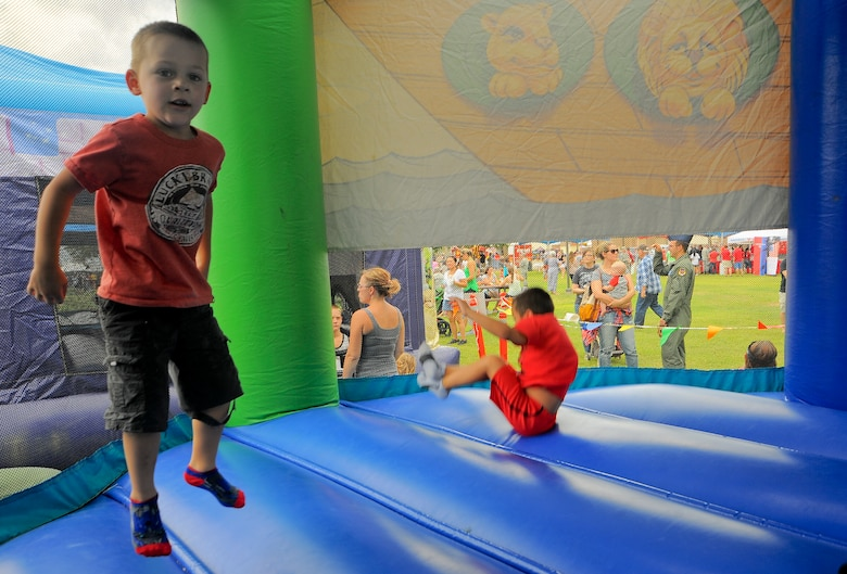"""Lucas Foote, son of U.S Air Force Senior Airman Jonathan Foote, 355th Maintenance Group, jumps in a bounce castle at the """"Welcome Home"""" Barbecue at Davis-Monthan Air Force Base, Ariz., Sept. 3, 2015. The barbecue was dedicated by the Tucson community to D-M Airmen and their families.  (U.S. Air Force photo by Airman 1st Class Mya M. Crosby/Released)"""