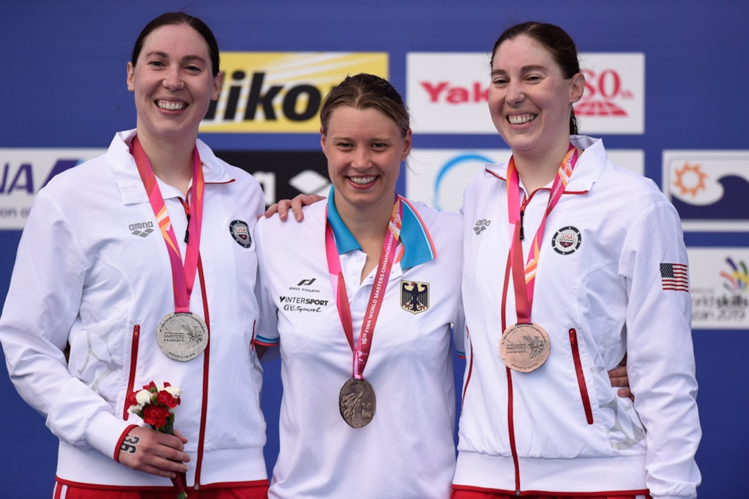First Lt. Sara Holman (left), 50th Operations Support Squadron payload systems operator instructor, Jenny Wachsmuth, German gold medal finisher, and 1st Lt. Mary Holman, 50th Operations Group evaluator, stand at the medal podium following the 3,000-meter open water swim Aug. 7, 2015, in Kazan, Russia. The Holman twins competed in the 2015 International Swimming Federation swim championship, earning a combined 12 top-10 finishes in seven events. (Courtesy Photo)