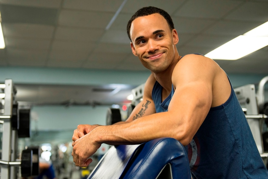 First Lt. Roman Tillman, 5th Space Launch Squadron responsible engineer, takes a break before performing more repetitions in his workout routine July 21, 2015, at the fitness center at Patrick Air Force Base, Fla. Tillman is a men's physique competitor working towards his International Federation of Body Building pro card. (U.S. Air Force photo by Matthew Jurgens/Released)
