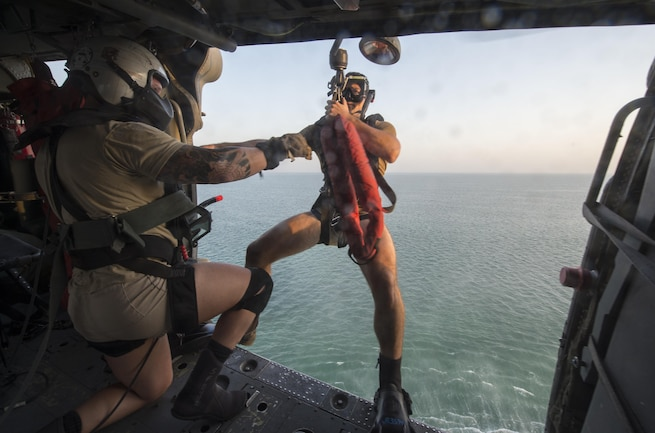 U.S. Navy Seaman Jason Rypkema prepares to exit an MH-60S Seahawk helicopter during search and rescue training with Helicopter Sea Combat Squadron 26 over the Arabian Gulf, Aug. 15, 2015. Rypkema is an aircrewman. Search and rescue swimmers play a key role in personnel safety and mission readiness of U.S. Navy operations. U.S. Navy photo by Petty Officer 1st Class Joshua Bryce Bruns