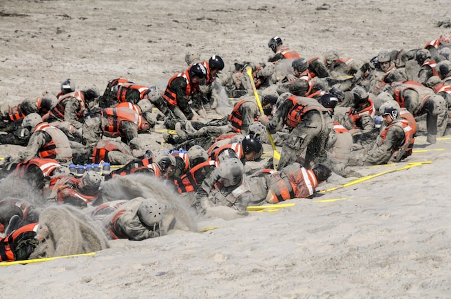 SEAL candidates for basic underwater demolition cover themselves in sand during surf passage on Naval Amphibious Base Coronado, Calif, Sept. 2, 2015. Surf passage is part of the first phase of SEAL training. U.S. Navy photo by Petty Officer 1st Class Michael Russell