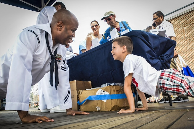 Navy Petty Officer 2nd Class Paul Donaldson executes a pushup with a child during a Navy air show in Atlantic City, N.J., Sept. 2, 2015. Donaldson is a master-at-arms and Navy recruiting scout from Navy Recruiting District Philadelphia. The annual event featured various flight demonstrations and the U.S. Navy Blue Angels. U.S. Navy photo by Petty Officer 1st Class Felicito Rustique