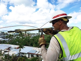 Delta Company's Cpl. David Schmidt repairs an electric line that powers water wells in the Gualo Rai area of Saipan.