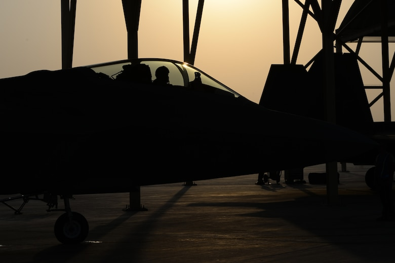 F-22 Raptors prepare to taxi at an undisclosed location in Southwest Asia, August 30, 2015. The F-22's combination of sensor capability, integrated avionics, situational awareness, and weapons provides first-kill opportunity against threats. (U.S. Air Force photo illustration/ Staff Sgt. Sandra Welch)
