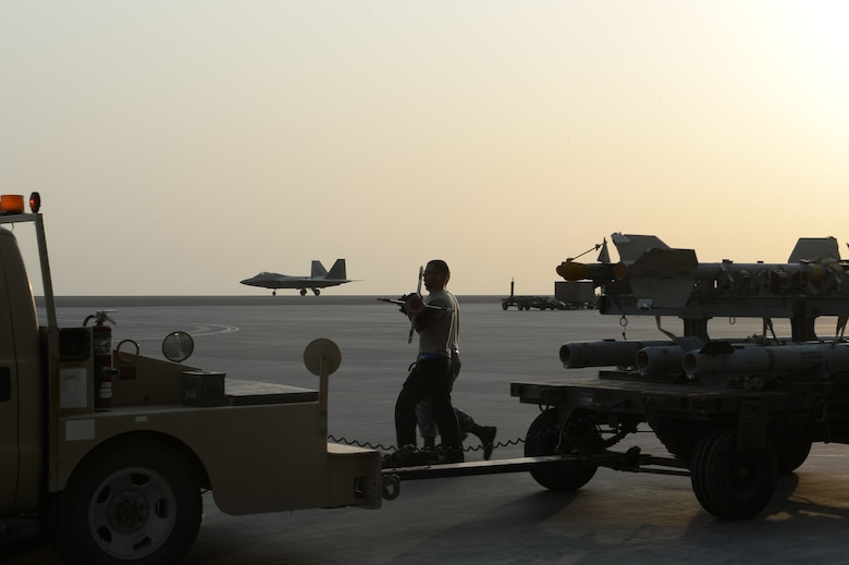 380th Expeditionary Maintenance Airmen prepare to load munitions on an F-22 Raptor while another F-22 Raptor taxis on the runway at an undisclosed location in Southwest Asia, August 30, 2015. The F-22's combination of sensor capability, integrated avionics, situational awareness, and weapons provides first-kill opportunity against threats. (U.S. Air Force photo/ Staff Sgt. Sandra Welch)