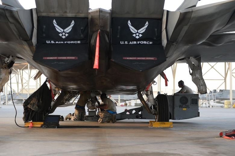380th Expeditionary Maintenance Airmen prepare to load munitions on an F-22 Raptor at an undisclosed location in Southwest Asia, August 30, 2015. The F-22's combination of sensor capability, integrated avionics, situational awareness, and weapons provides first-kill opportunity against threats. (U.S. Air Force photo illustration/ Staff Sgt. Sandra Welch)