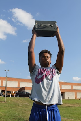 Chance Hagwood, a high school senior and Bassett native, performs the ammo can lift during the Marine Corps Combat Fitness Test, Aug. 27, 2015. The Bassett High School football team took part in the CFT in place of one of their normal practices, giving them a different workout than they are used to and challenging them in ways they've never been challenged. (U.S. Marine Corps photo by Sgt. Aaron Diamant/Released)