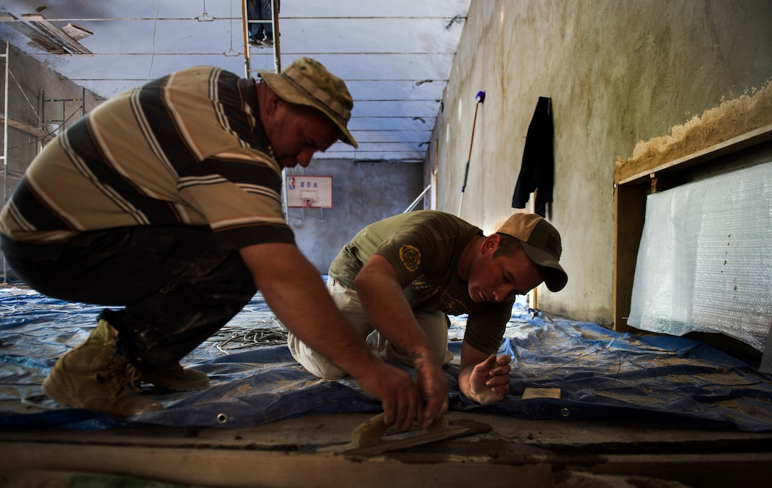 Staff Sgt. David Dengate, a 435th Construction and Training Squadron pavement and equipment operator, works with a Georgian army engineer to help fill in concrete in the entrance to the gymnasium of Public School No. 4 in Gori, Georgia, Aug. 27, 2015. Air Force and Georgian army engineers sometimes worked 16-hour days during a 30-day school renovation project that will help the children of Gori. Humanitarian and civic assistance projects enhance operational readiness of military personnel while providing mutual support to the host nation's population. (U.S. Air Force photo/Staff Sgt. Sara Keller)