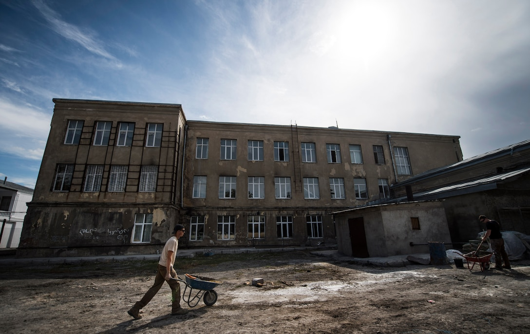 Airman 1st Class Cole Kasten, a 52nd Civil Engineer Squadron pavement and heavy equipment operator, pushes a wheel barrel before mixing cement for a ramp at Public School No. 4 in Gori, Georgia, Aug. 28, 2015. Kasten, along with a six-person Air Force team and Georgian army engineers, sometimes worked 16-hour days during a 30-day school renovation project that will help the children of Gori. Humanitarian and civic assistance projects enhance operational readiness of military personnel while providing mutual support to the host nation's population. (U.S. Air Force photo/Staff Sgt. Sara Keller)