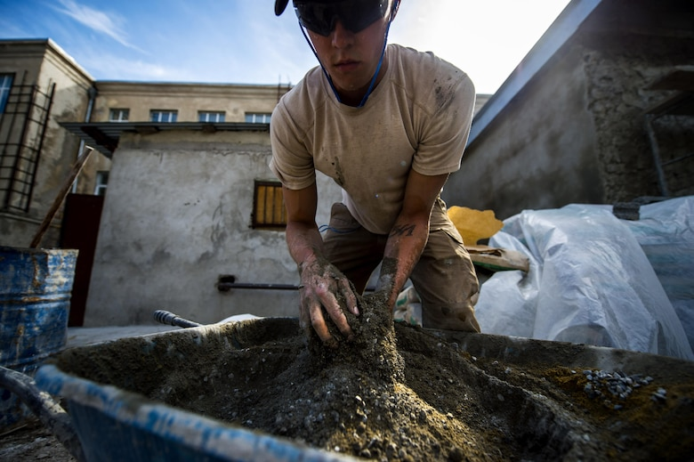 Airman 1st Class Cole Kasten, a 52nd Civil Engineer Squadron pavement and heavy equipment operator, mixes cement for a ramp at Public School No. 4 in Gori, Georgia, Aug. 28, 2015. Kasten and a team of Airmen built a ramp to give disabled students at the school safe access into the gymnasium. Humanitarian and civic assistance projects enhance operational readiness of military personnel while providing mutual support to the host nation's population. (U.S. Air Force photo/Staff Sgt. Sara Keller)