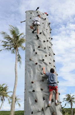 Andersen family members tackle a rock climbing wall at the Labor Day Bash Sept. 4, 2015, on Andersen Air Force Base, Guam. The event included family friendly activities such as rock wall climbing, zip lining, carabao rides, dance-off contests and a Mockingbird Sun concert at the end. (U.S. Air Force photo by Airman 1st Class Arielle Vasquez/Released)