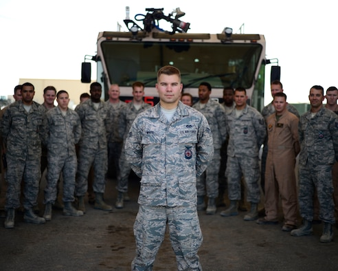 U.S. Air Force Senior Airman Zach White, 332nd Expeditionary Civil Engineer Squadron fire truck engineer and driver operator, stands in front of his fire fighter comrades at an undisclosed location in Southwest Asia, Aug. 20, 2015. White dedicated his spare time during his deployment by running 150 miles to raise $2,500 to sponsor an athlete for the 2017 Special Olympics. (U.S. Air Force photo by Senior Airman Racheal E. Watson/Released)