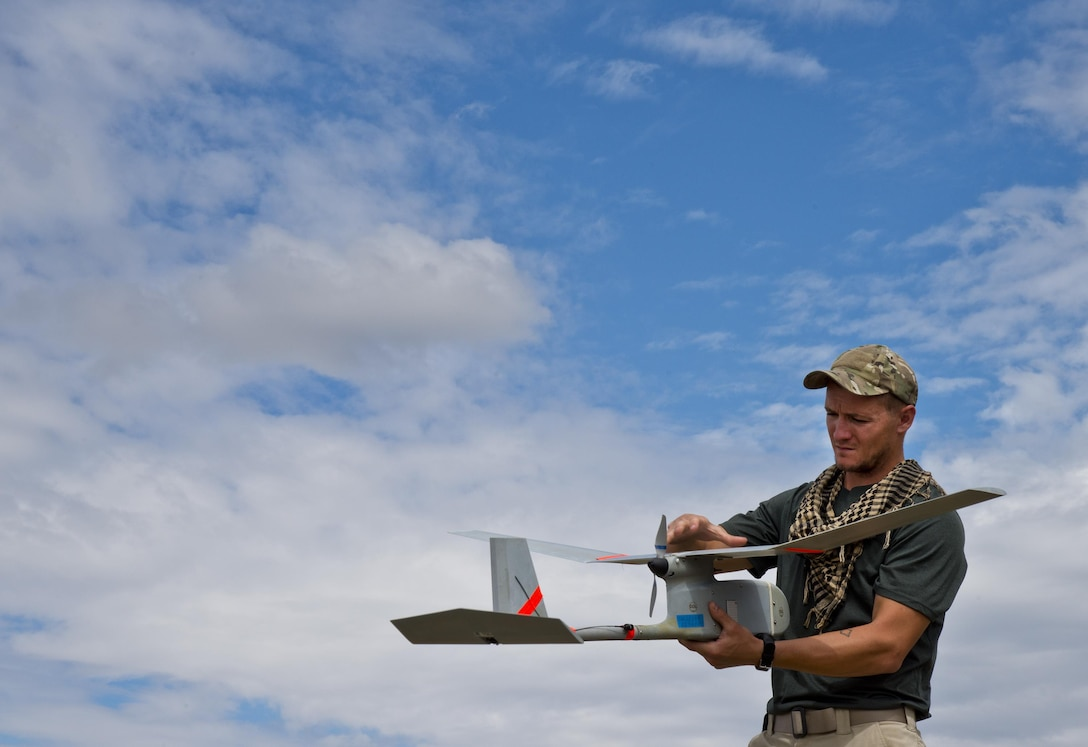 Staff Sgt. Leland Hastings, 919th Special Operations Security Forces Squadron, prepares to launch the Raven-B, a four-by-four foot unmanned aerial system, into the skies above Camp Guernsey, Wyo., Aug. 4.  The 919th SOSFS brought the UAS to demonstrate its capabilities to other security forces units involved in a large field training exercise at the camp. The Raven-B has the ability to take photos, video in day or night, and even designate locations via an IR laser.  It also provides coordinates, magnetic azimuths, and linear distances creating a birds-eye view to topographical map. (U.S. Air Force photo/Tech. Sgt. Sam King)
