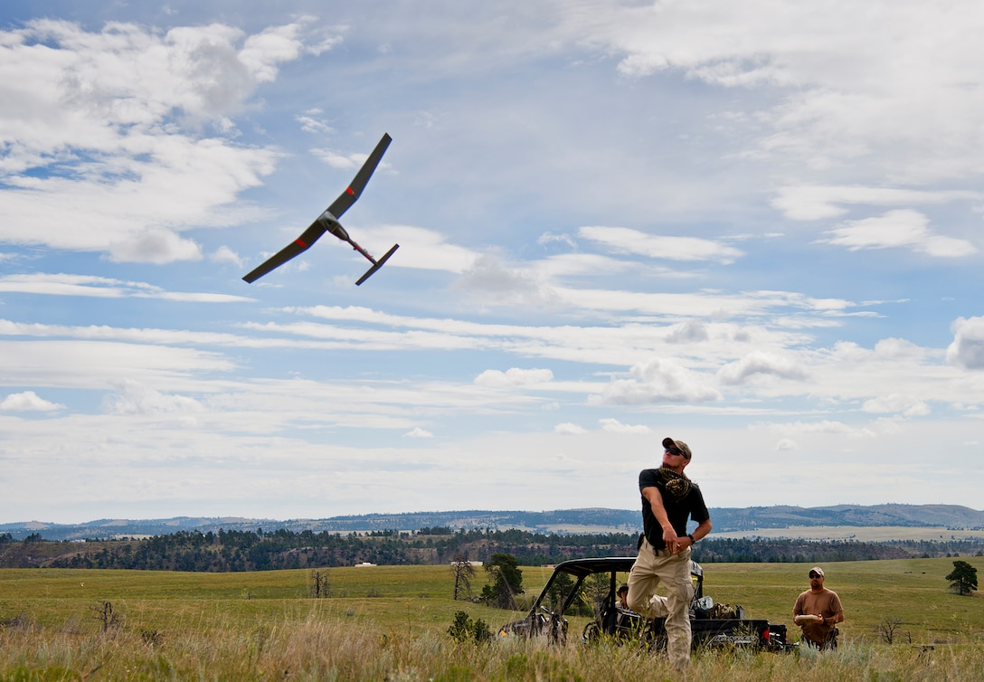 Staff Sgt. Leland Hastings, 919th Special Operations Security Forces Squadron, launches Raven-B, a four-by-four foot unmanned aerial system, into the skies above Camp Guernsey, Wyo., Aug. 4.  The 919th SOSFS brought the UAS to demonstrate its capabilities to other security forces units involved in a large field training exercise at the camp. The Raven-B has the ability to take photos, video in day or night, and even designate locations via an IR laser.  It also provides coordinates, magnetic azimuths, and linear distances creating a birds-eye view to topographical map. (U.S. Air Force photo/Tech. Sgt. Sam King)