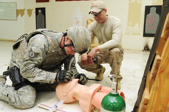 Staff Sgt. Derek Ables (left), 21st Security Forces Squadron, establishes an airway on a simulated patient using a nasopharyngeal tool during a pilot course for Tactical Combat Casualty Care on Aug. 7, 2015 at Peterson Air Force Base, Colo. Tech. Sgt. Bradley Belcher, 302nd Aeromedical Staging Squadron, instructed the T-CCC beta course for non-medical personnel in order to help eliminate preventative deaths on the battlefield. (U.S. Air Force photo/Senior Airman Amber Sorsek)