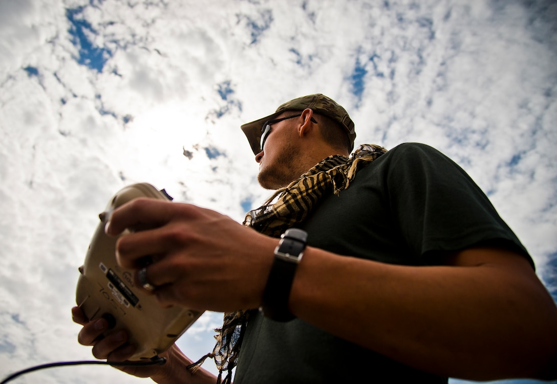 Staff Sgt. Leland Hastings, 919th Special Operations Security Forces Squadron, controls the Raven-B, a four-by-four foot unmanned aerial system, via remote control at Camp Guernsey, Wyo., Aug. 4.  The 919th SOSFS brought the UAS to demonstrate its capabilities to other security forces units involved in a large field training exercise at the camp. The Raven-B has the ability to take photos, video in day or night, and even designate locations via an IR laser.  It also provides coordinates, magnetic azimuths, and linear distances creating a birds-eye view to topographical map. (U.S. Air Force photo/Tech. Sgt. Sam King)