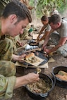 Australian Army LT Ben Peterson and U.S. Army soldiers with the 25th Infantry Division, U.S. Army Pacific, serves eat beef stew cooked in a camp oven during Exercise Kowari 2015, being held in the Daly River region of the Northern Territory. Kowari is a trilateral environmental survival training opportunity hosted by Australia and includes forces from Australia, China and the U.S. simultaneously.