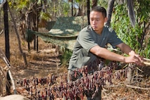 Chinese People's Liberation Army soldier Staff Sergeant Zhu Jiang Tao dries meat during Exercise Kowari 2015, being held in the Daly River region of the Northern Territory. Kowari is a trilateral environmental survival training opportunity hosted by Australia and includes forces from Australia, China and the U.S. simultaneously.