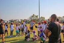 U.S. Marines with Marine Rotational Force – Darwin, listen to the training schedule while participating in a softball clinic for local youth July 23 at Tracy Village Social and Sports Club, Wanguri, Northern Territory, Australia. The Marines supported the supported the U.S. State Department-sponsored community event with the Northern Territory's school softball program to mentor the students and teach them how to play competitively. Beyond purely military training, Marines' involvement in community engagements in the Northern Territory shows their appreciation for Australia's hospitality.
