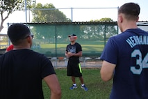 U.S. Marine Corps Gunnery Sgt. Pedro Chamorro, a supply chief with Marine Heavy Helicopter Squadron 463, Marine Rotational Force – Darwin and a native of Miami, discusses teamwork with Marines during a softball clinic for local youth July 25 at Tracy Village Social and Sports Club, Wanguri, Northern Territory, Australia. The Marines supported the U.S. State Department-sponsored community event with the Northern Territory's school softball program to mentor the students and teach them how to play competitively. Beyond purely military training, Marines' involvement in community engagements in the Northern Territory shows their appreciation for Australia's hospitality.