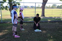 U.S. Marine Corps Cpl. Joseph Chaparro, an aircraft rescue and firefighting specialist with Marine Wing Support Squadron 171, Marine Rotational Force – Darwin, explains techniques for the catcher position during a softball clinic for local youth July 25 at Tracy Village Social and Sports Club, Wanguri, Northern Territory, Australia. The Marines supported the U.S. State Department-sponsored community event with the Northern Territory's school softball program to mentor the students and teach them how to play competitively. Beyond purely military training, Marines' involvement in community engagements in the Northern Territory shows their appreciation for Australia's hospitality.