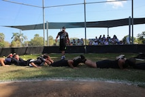 U.S. Marines with Marine Rotational Force – Darwin conduct squad push-ups to demonstrate a team-building exercise during a softball clinic for local youth July 25 at Tracy Village Social and Sports Club, Wanguri, Northern Territory, Australia. The Marines supported the U.S. State Department-sponsored community event with the Northern Territory's school softball program to mentor the students and teach them how to play competitively. Beyond purely military training, Marines' involvement in community engagements in the Northern Territory shows their appreciation for Australia's hospitality.