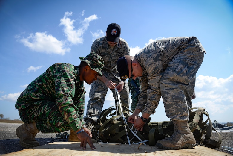U.S. Air Force Captains Jay Bateman, 736th Security Forces Squadron director of operations, right, and Christopher Baird,  621st Mobility Support Operations Squadron air mobility liaison, untangle airdrop rigging with the help of a Falintil Forças de Defesa de Timor-Leste soldier Sept. 8, 2015, in Baucau, Timor-Leste. The rigging material contained rice packages that were airdropped by a North Carolina Air National Guard C-130 Hercules during Operation Pacific Angel 15-2. Efforts undertaken during Pacific Angel help multilateral militaries in the Pacific improve and build relationships across a wide spectrum of civic operations, which bolsters each nation's capacity to respond and support future humanitarian assistance and disaster relief operations. (U.S. Air Force photo by Staff Sgt. Alexander W. Riedel/Released)