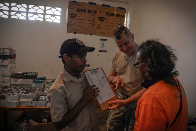 U.S. Air Force Master Sgt. Robert Shaw (center), 141st Medical Group NCO in charge of optometry, shows a patient his vision results during an Operation Pacific Angel health services outreach event Sept. 7, 2015, in Baucau, Timor-Leste. Pacific Angel is a multilateral humanitarian assistance civil military operation, which improves military-to-military partnerships in the Pacific while also providing medical health outreach, civic engineering projects and subject matter exchanges among partner forces. (U.S. Air Force photo by Staff Sgt. Alexander W. Riedel/Released)