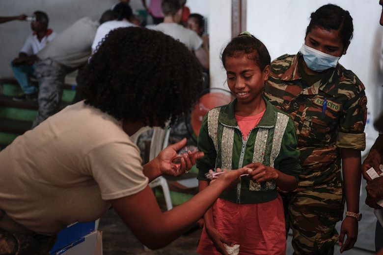 U.S. Air Force Staff Sgt. Latrisha Skinner (left), 35th Aerospace Medicine Squadron optometry technician, offers a choice of sunglasses to a young patient following her optometry examination during an Operation Pacific Angel 15-2 health services outreach event Sept. 7, 2015, in Baucau, Timor-Leste. Pacific Angel is a multilateral humanitarian assistance civil military operation, which improves military-to-military partnerships in the Pacific while also providing medical health outreach, civic engineering projects and subject matter exchanges among partner forces. (U.S. Air Force photo by Staff Sgt. Alexander W. Riedel/Released)