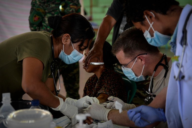 U.S. Air Force Maj. Richard Trowbridge (right), family practice physician assigned to the 374th Medical Group at Yokota Air Base, Japan, extracts a cyst from a patient's arm with Falintil-Forças de Defesa de Timor-Leste 2nd Lt. Anabela de Cruz (left), during an Operation Pacific Angel 15-2 health services outreach clinic Sept. 7, 2015, in Baucau, Timor-Leste. Pacific Angel is a multilateral humanitarian assistance civil military operation, which improves military-to-military partnerships in the Pacific while also providing medical health outreach, civic engineering projects and subject matter exchanges among partner forces. (U.S. Air Force photo by Staff Sgt. Alexander W. Riedel/Released)
