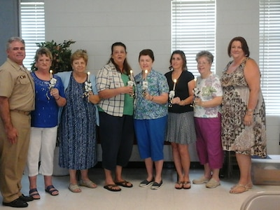 U.S Navy Captain, Tim Sparks, Joint Base Charleston deputy commander (left) and Sheryl Bice, NWCA Eastern Region President (right) installed the new officers of the Navy Wives Clubs of America MenRiv Park #240. Hazel Cole, Gina Kane, Fawn Hersman, Jan Hill, Nancy Tarwarter, and Linda Hedden.