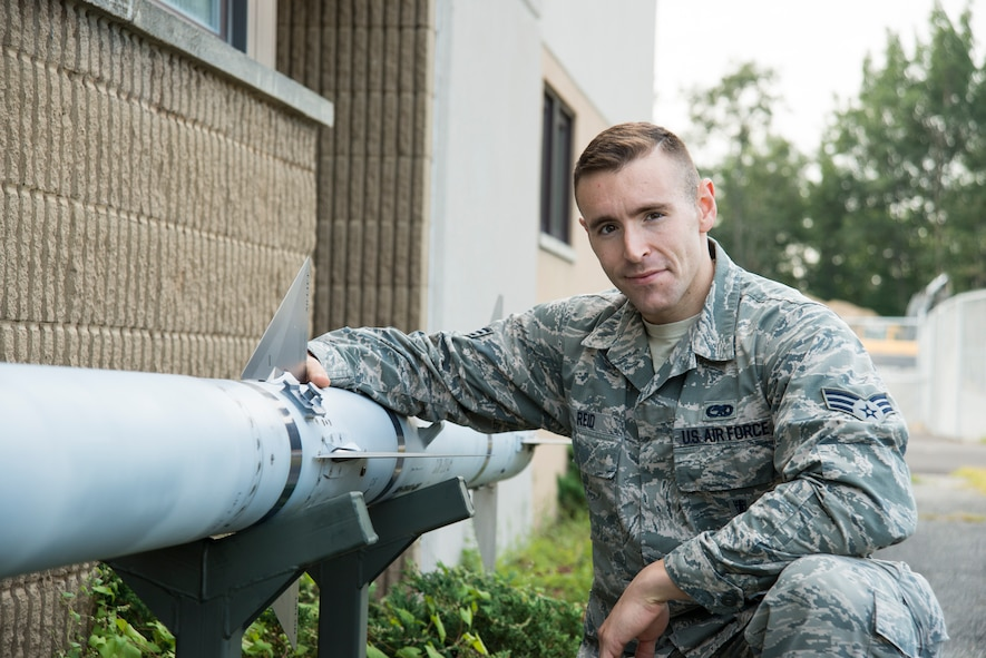 U.S. Air Force Senior Airman Griffin Reid poses beside a static display missile at the Vermont Air National Guard base Sept. 2, 2015. When not on military duty, he helps people who have spent time in jail reintegrate back into the community. (U.S. Air National Guard photo by Airman 1st Class Jeffrey Tatro)